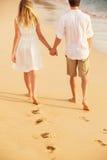 在爱的年轻夫妇在海滩日落 库存图片