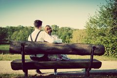 在爱的年轻夫妇坐一条长凳在公园 葡萄酒 免版税库存图片