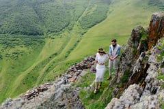 在爱的年轻夫妇,享受他们的在山的旅行 与大美丽的山的侧视图在前景 免版税库存照片