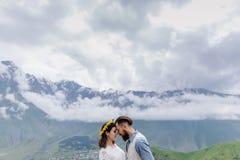 在爱的年轻夫妇,看彼此,衣服的一个白色的人和女孩与花,站立户外 免版税库存照片