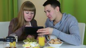 在爱的年轻快乐的夫妇看片剂和谈话在早餐 股票视频