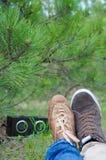 在爱的年轻愉快的夫妇坐地面和听的音乐在绿色夏天公园 免版税库存照片