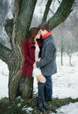 在爱的年轻有吸引力的夫妇在树附近的街道上 免版税图库摄影
