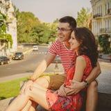 在爱笑的拥抱的逗人喜爱的年轻微笑的夫妇,坐户外在绿色城市街道,夏令时 库存图片