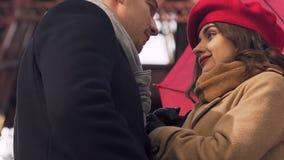 在爱见面的夫妇室外,亲吻在伞后,女性深色的约会 股票录像