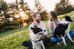 在爱走的狗和结合的浪漫夫妇 免版税库存图片
