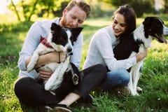 在爱走的狗的浪漫夫妇本质上和微笑 免版税库存图片