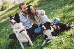 在爱走的狗的浪漫夫妇本质上和微笑 免版税图库摄影