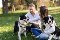 在爱走的狗的浪漫夫妇本质上和微笑 免版税库存照片