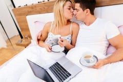 在爱饮用的早晨咖啡的夫妇在床上 免版税库存图片