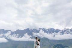 在爱,拥抱,一个人衣服的和女孩的年轻夫妇与花的白色的, 图库摄影