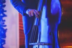 在爵士乐队执行期间,与歌唱者和音乐会共同安排观点的一个最低音大提琴球员 免版税库存图片