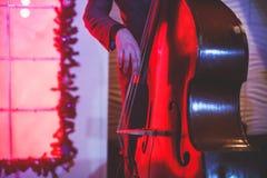 在爵士乐队执行期间,与歌唱者和音乐会共同安排观点的一个最低音大提琴球员 图库摄影