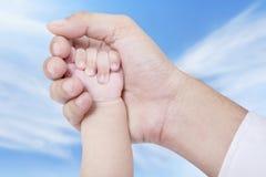 在父亲棕榈的婴孩手 免版税库存照片