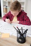 在父亲` s工商业票据的年轻男孩图画在办公室 免版税库存照片