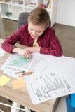 在父亲` s工商业票据的年轻男孩图画在办公室 库存照片