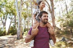 在父亲` s肩膀的女儿骑马在乡下步行 图库摄影