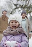 在父母前面的女孩运载的雪球在公园在冬天 免版税库存图片