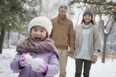 在父母前面的女孩运载的雪球在公园在冬天 库存图片