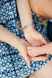 在父母的手上的婴孩赤裸腿 图库摄影