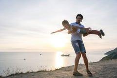 在爸爸` s手上的儿子在与海边的一座山飞行 一起使用在日落 乐趣消遣 免版税图库摄影