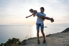 在爸爸` s手上的儿子在与海边的一座山 一起使用在日落 乐趣消遣 免版税库存照片