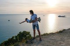 在爸爸` s手上的儿子在与海边的一座山 一起使用在日落 乐趣消遣 图库摄影