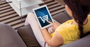 在片剂个人计算机的妇女感人的购物车象 免版税库存照片