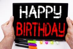 在片剂写的生日快乐文本,计算机在有标志的,笔,文具办公室 周年著名人士的企业概念 免版税库存照片