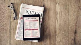 在片剂和报纸的读书新闻在木背景 免版税库存照片