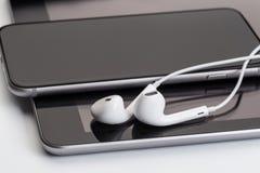 在片剂和电话的白色耳机 库存照片