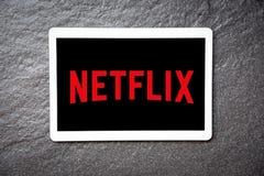 在片剂服务观看的娱乐和电影的Netflix应用程序与Netflix商标 库存图片