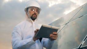 在片剂的一位工程师类型,站起来在屋顶的太阳盘区附近,关闭 影视素材