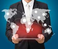 在片剂的商人常设姿势手举行地球地图 库存照片