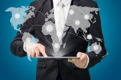 在片剂的商人常设姿势手举行地球地图 图库摄影