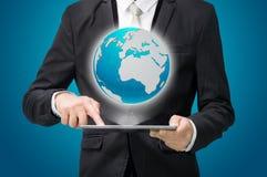 在片剂的商人常设姿势手举行地球地图 免版税库存照片