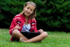 在片剂的女孩愉快的研究 免版税库存图片
