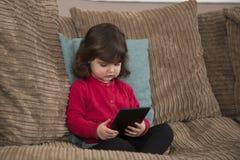 在片剂的女孩观看的动画片 免版税库存图片