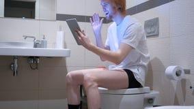 在片剂的录影闲谈由人坐卫生间洗脸台 图库摄影