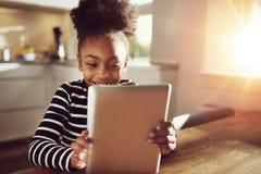 在片剂的愉快的矮小的种族黑女孩读书 免版税图库摄影