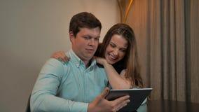 在片剂的有吸引力的夫妇海浪在家 股票录像