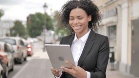 在片剂的网上视频聊天由非洲女实业家,站立室外由路 影视素材