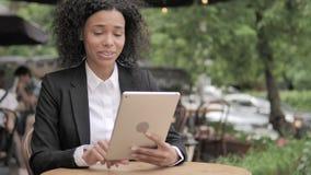 在片剂的网上视频聊天由非洲妇女,坐在室外咖啡馆 影视素材
