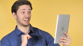 在片剂的网上视频聊天由黄色背景的偶然年轻人 影视素材