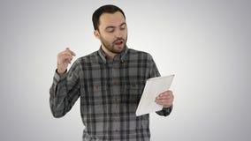在片剂的网上视频聊天通过走梯度背景的人 免版税库存图片