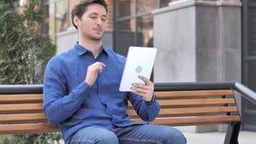 在片剂的视频聊天由年轻人坐长凳 影视素材