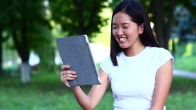 在片剂的年轻美好的亚洲人谈话在绿色公园摇手 影视素材