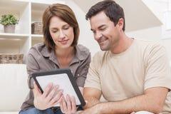 在片剂计算机上的男人&妇女夫妇在家 免版税库存照片