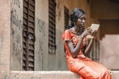 在片剂计算机上的非洲黑种族妇女读书 免版税库存照片