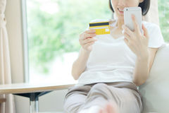 在片剂计算机和信用卡上的妇女购物 免版税库存照片